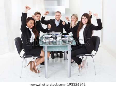Portrait of successful business team with arms raised sitting at desk at office - stock photo