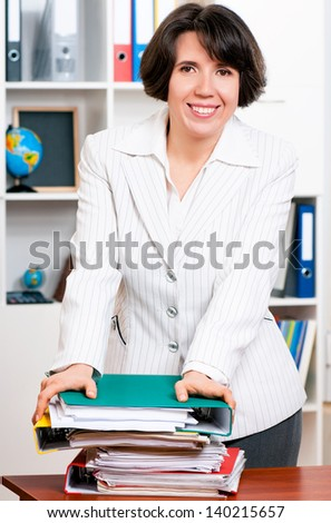 Portrait of successful business woman or teacher with folders at her office
