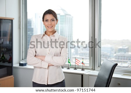 Portrait Of Successful Business Woman With Arm Crossed In Office. - stock photo