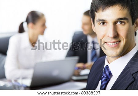 Portrait of successful businessman and colleagues on background, at office - stock photo