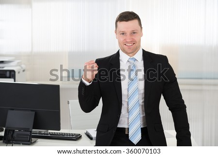 Portrait of successful businessman clenching fist while standing at computer desk in office