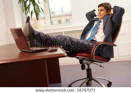 Portrait of successful businessman having rest on workplace in office - stock photo