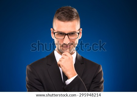Portrait of successful businessman in black suit on blue background. Short-haired man in glassess smiling and touching his chin. - stock photo