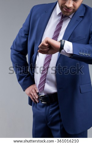 Portrait of successful businessman is waiting for his business partner. He is standing and looking at his watch with disappointment. Isolated on background - stock photo
