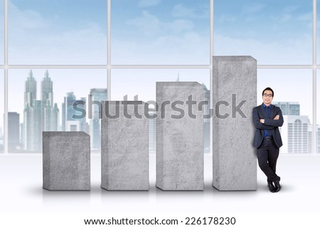 Portrait of successful businessman lean on business growth chart in office - stock photo