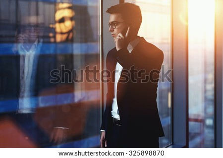 Portrait of successful businessman talking on mobile phone while standing against window in hallway of modern office interior, young confident man having cell telephone conversation during work break - stock photo
