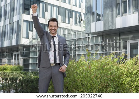 Portrait of successful businessman with arm raised standing outside office building - stock photo