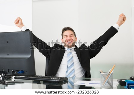 Portrait of successful businessman with arms raised at desk in office - stock photo