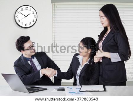 Portrait of successful businesswoman closing a meeting and shaking hands with her partner in the office - stock photo