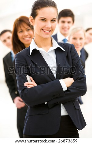 Portrait of successful businesswoman looking at camera on background of several employees - stock photo