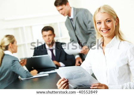 Portrait of successful businesswoman sitting at the table in a working environment