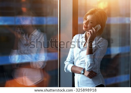 Portrait of successful businesswoman talking on her cellphone while standing near big window in modern office interior, young female entrepreneur making a call on her smart phone with her best friend  - stock photo