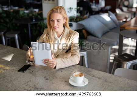 Portrait of successful businesswoman working at cafe