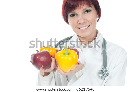 Portrait of successful cute young female doctor holding fresh fruits and vegs. Healthy-eating concept - stock photo