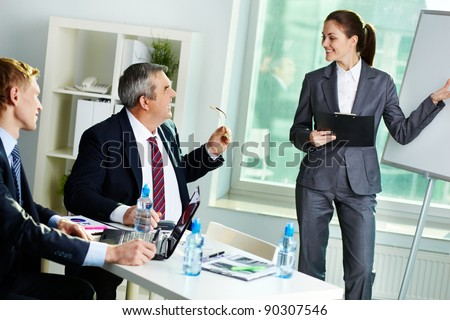 Portrait of successful female presenting her project at seminar in office - stock photo