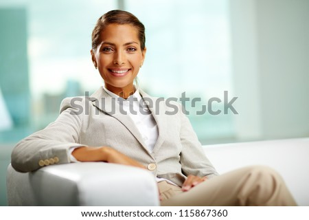 Portrait of successful female sitting in office - stock photo