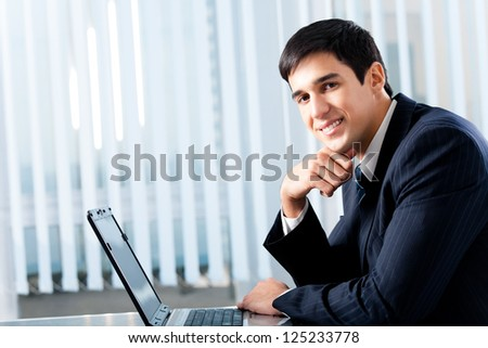 Portrait of successful happy smiling business man working with laptop at office, with copyspace - stock photo