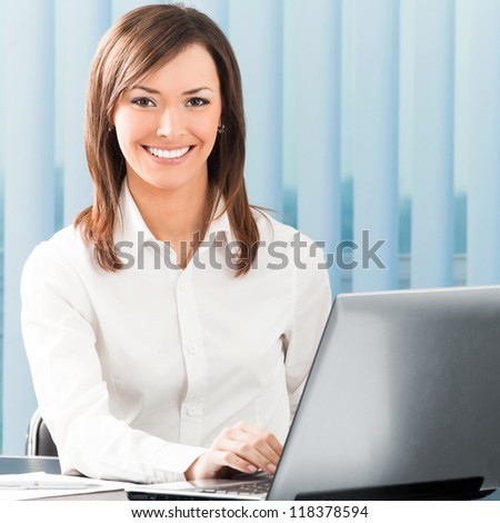 Portrait of successful happy smiling business woman working with laptop at office - stock photo