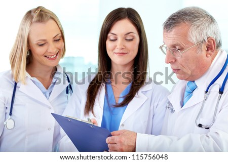 Portrait of successful medical workers discussing plan in hospital