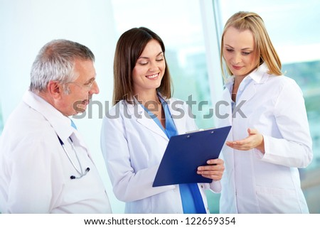 Portrait of successful medical workers discussing plan in hospital - stock photo