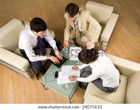 Portrait of successful people sitting on the armchair and discussing - stock photo
