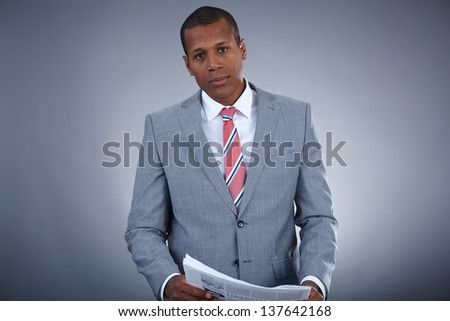Portrait of successful professional in suit with newspaper looking at camera - stock photo