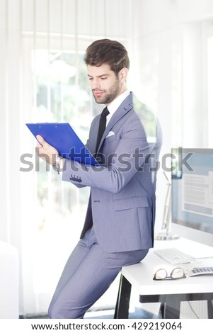 Portrait of successful sales man holding clipboard in his hand while working at office.