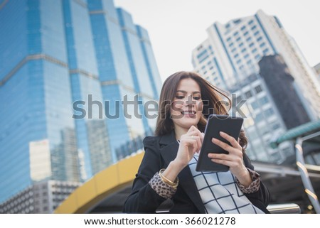 Portrait of successful smart business woman looking confident and smiling holding tablet computer - stock photo