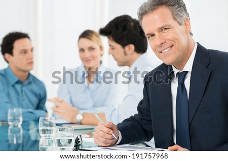 Portrait Of Successful Smiling Mature Businessman Looking At Camera - stock photo
