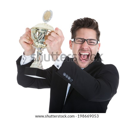 Portrait of successful young businessman holding trophy over white background