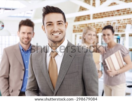 Portrait of successful young businessman, smiling, looking at camera. - stock photo