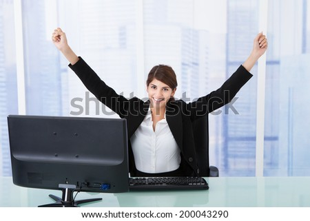 Portrait of successful young businesswoman with arms raised at computer desk