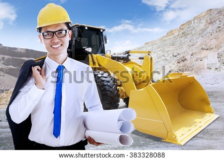 Portrait of successful young foreman smiling at the camera with blueprint and backhoe on the construction site - stock photo