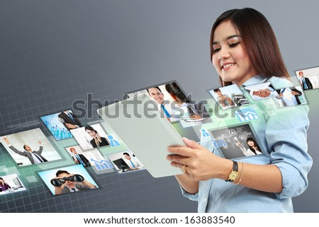 Portrait of successful young woman with tablet on virtual background - stock photo
