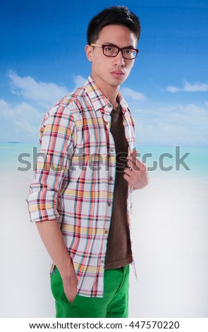 portrait of sunny man wearing sunglasses on a blue sky background - stock photo
