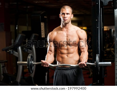 Portrait of super fit muscular young man working out in gym. - stock photo