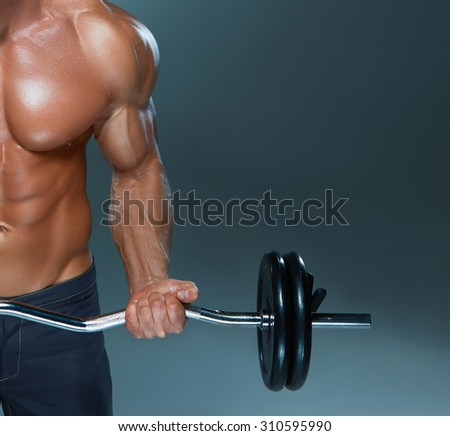 Portrait of super fit muscular young man working out in gym with barbell on gray background, copyspace image - stock photo