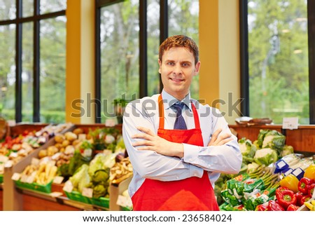 Portrait of supermarket store manager in front of fresh vegetables - stock photo