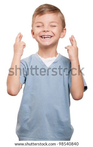 Portrait of superstitious little boywith crossed fingers over white background - stock photo