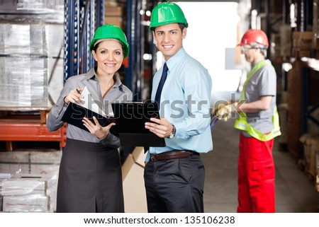 Portrait of supervisors with clipboard and foreman unloading cardboard boxes at warehouse - stock photo