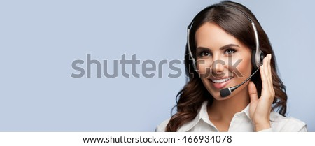 Portrait of support female phone operator in headset, with blank copyspace area for slogan or text message, on grey background. Consulting and assistance service call center.