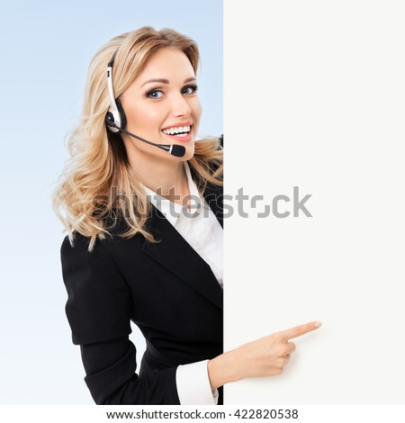 Portrait of support phone operator in headset showing blank signboard with copyspace area for text or slogan, on blue background