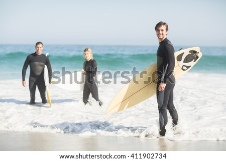 Portrait of surfer friends with surfboard standing on the beach on a sunny day - stock photo