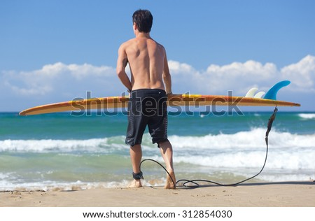 Portrait of Surfer with longboard on the beach. - stock photo