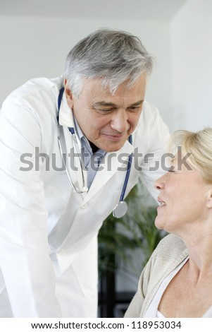 Portrait of surgeaon talking to patient in wheelchair