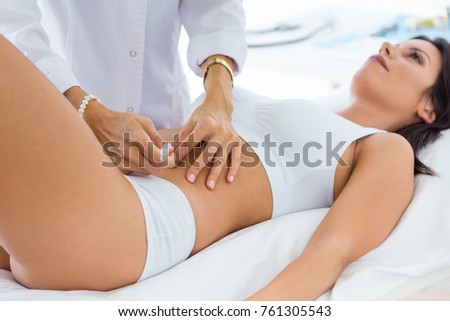 Portrait of surgeon making injection into female body. Liposuction concept.