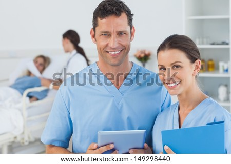 Portrait of surgeons in bright surgery with doctor attending patient on background - stock photo