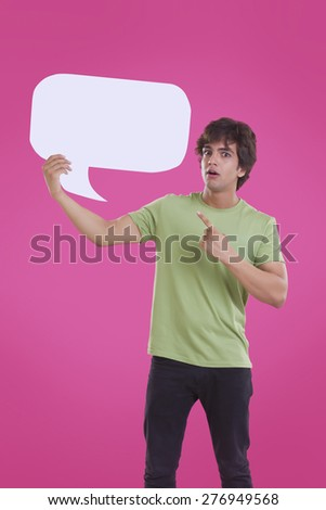 Portrait of surprise young man pointing at speech bubble over pink background - stock photo