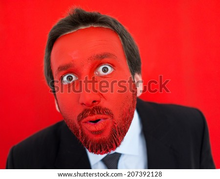 Portrait of surprised adult man with red painted face