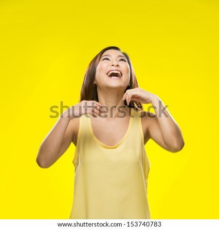 Portrait of surprised Asian Woman. Young fresh Chinese female model on bright orange background.